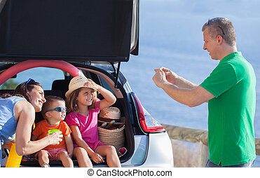 family summer holiday sitting in car.