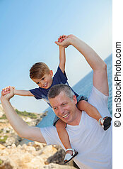 father and son piggyback on vacation