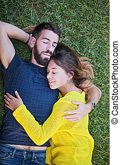 couple in love laying on grass in summer