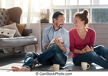 Middle-aged couple sitting on floor near window