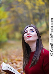 Portrait of beautiful young brunette girl reading a book in...