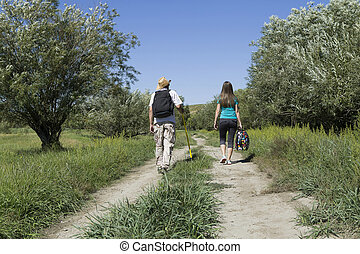 Rear view of a romantic couple of tourists walking in love -...