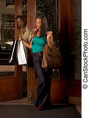 Black woman with shopping bags man looking at her -...