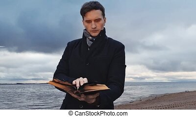 Young man reading burning book standing on coast storm clouds on background