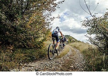 group of cyclists on sports mountainbike riding uphill....