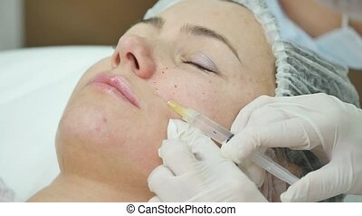 Beautiful young woman is getting botox injection at clinic. She is sitting and smiling. The doctor is holding syringe near her eyebrows carefully