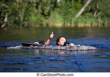 brunette woman riding wakeboard in a summer lake - Young...