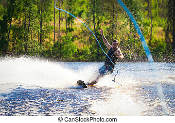 Young man riding wakeboard on summer lake - Young man riding...