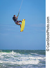 Athletic man jump on kite surf board sea waves - Athletic...