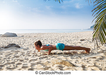 Young pretty slim brunette woman practise yoga pose tropical...