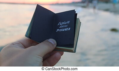 Explore Dream Discover - book with an inscription and the sunset on the beach. Travel book idea.
