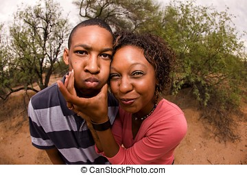 African-American family making faces - single-parent mom and...