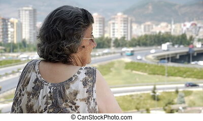 Old retired woman watching traffic from balcony - Retirement...