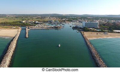 Flying above the entrance to the port, with a yacht marina....