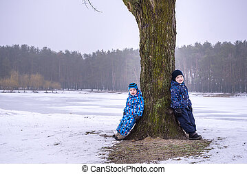 Happy family: two little siblings boys having fun in autumn winter forest.