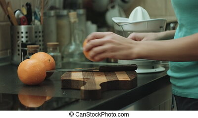 Woman cut oranges - Close-up shot of the woman on kitchen...