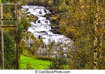 waterfall in autumn landscape in daytime