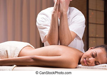 Deep tissue massage - Male professional masseur doing deep...