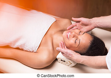 Woman receiving face massage in luxury spa