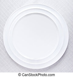 Empty white plate on tablecloth