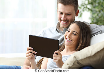 Couple watching media in a tablet - Casual couple watching...