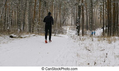male athlete runner running a winter marathon in a snowy...