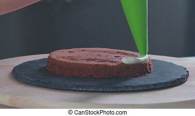 Chocolate cake. Confectioner covers chocolate cake creamy...