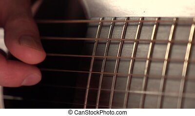 Man playing the guitar. Trembling strings. Super slow motion...