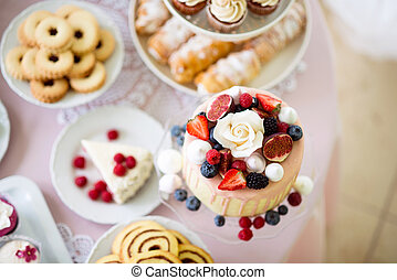 Cake with various berries and meringues on a stand....