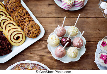 Table with cakepops, cookies and cupcakes. Wooden...