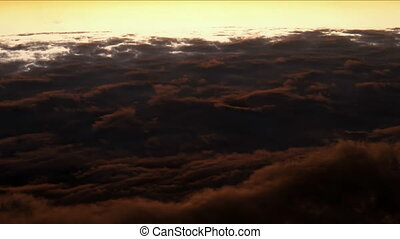 Flight above fluffy clouds - Sunset over clouds. From day to...