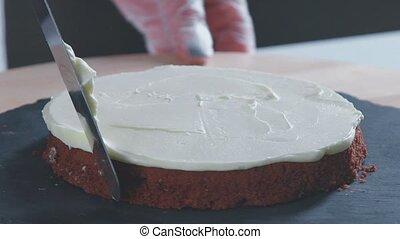 Confectioner equates biscuit cream using pastry spatula. -...