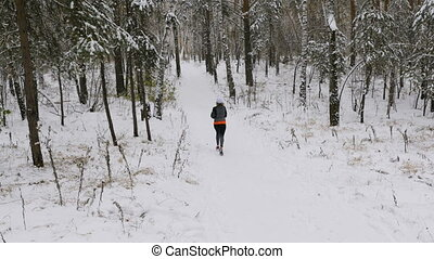 young female athlete runner running a winter marathon in a...