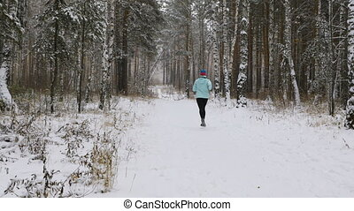 female athlete runner running a winter marathon in a snowy...