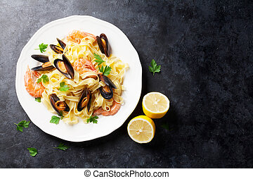 Pasta with seafood on stone table. Mussels and prawns. Top...