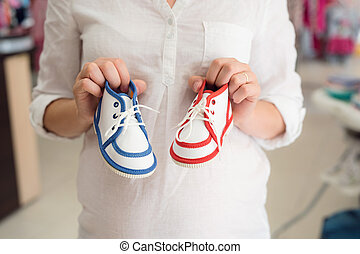 Unrecognizable pregnant woman shopping shoes for her baby -...