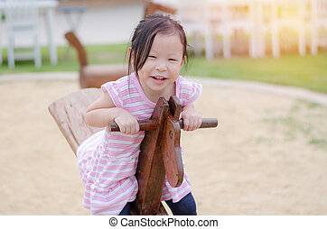 girl playing totter at playground - Little asian girl...