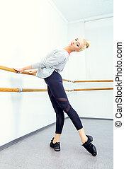 warming up - Modern ballet dancer in a ballet class.