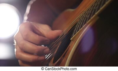Performing chords on acoustic guitar - Close up of guitarist...