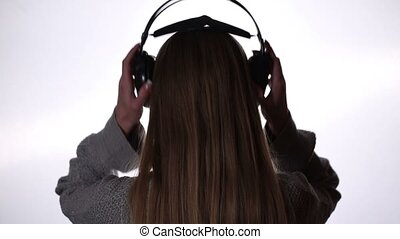 Young woman relaxing with music in headphones - Back view of...