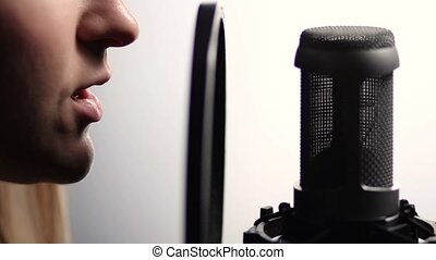 Woman profile singing into studio microphone