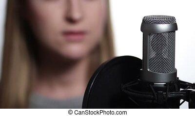 Closeup female singer recording track in studio - Close up...