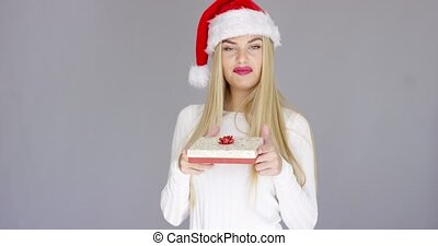 Pretty young girl posing with chrismas present while...