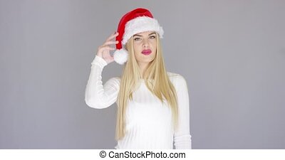 Adorable young woman posing in Santa Claus Hat over gray...