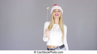 Pretty blond girl enjoy chrismas with sparkler. She wearing...