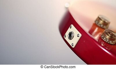 Plugging in cord into jack of electric guitar. - Close up of...