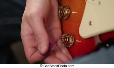 Tone knobs and volume of electric guitar - Close up of man's...
