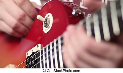 Rock musician with electric guitar fretting chord - Close up...