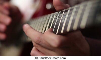 Guitar player using tapping technique. Close up of man using...