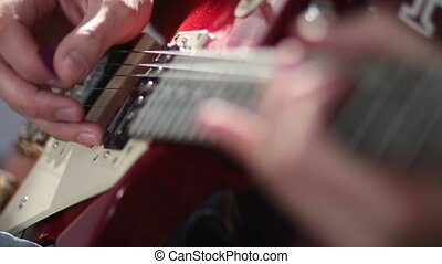 Guitarist hand strumming at electric guitar string - Close...